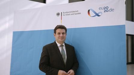 Hubertus Heil steht vor einem Aufsteller mit EU2020-Logo
