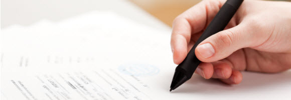 Hand hält schwarzen Stift zum Schreiben.