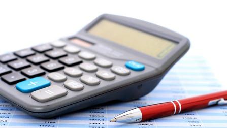 Ein Taschenrechner und ein Stift auf einem Papier mit Zahlen.