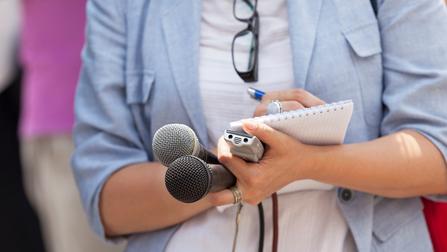 Eine Frau hält zwei Mikrofone, ein Diktiergerät, Notizblock und Stift in der Hand.
