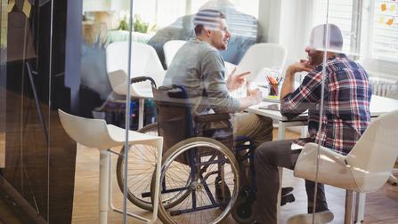 Ein Mann im Rollstuhl unterhält sich mit einem anderen Mann an einem Tisch.