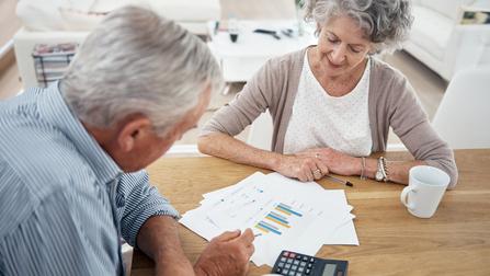 Zwei Rentner sitzen an einem Tisch und überprüfen Unterlagen.