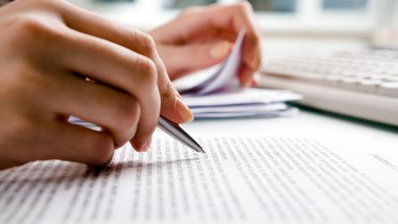 Eine Hand hält einen Stift über einem Papier.