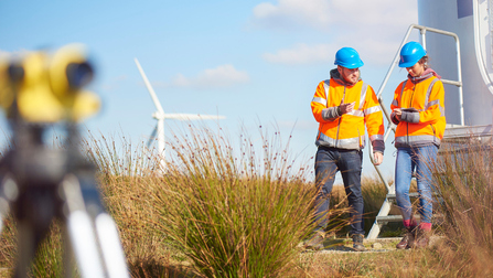 Windfarm mit zwei Arbeitern.