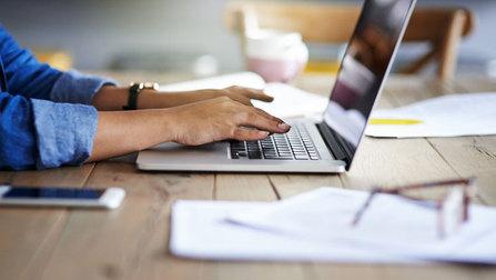 Eine Frau tippt auf einem Laptop.