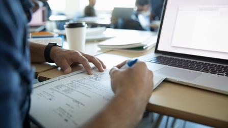 Ein junger Mann bearbeitet in einem Klassenzimmer Übungsaufgaben.