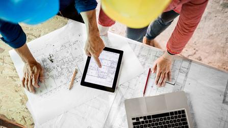 Zwei Arbeiter besprechen einen Bauplan.