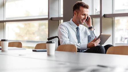 Ein Geschäftsmann sitzt im Rollstuhl mit einem Tablet und einem Smartphone in der Hand.