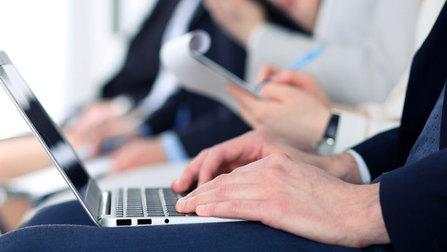 Ein Mann mit einem Laptob auf dem Schoß in einer Konferenz.