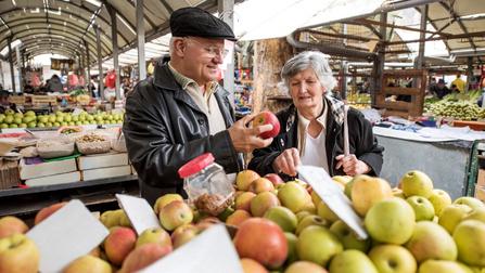 Zwei Rentner kaufen Äpfel am Marktstand.