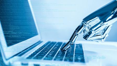 Eine Roboterhand tippt auf einem Laptop.
