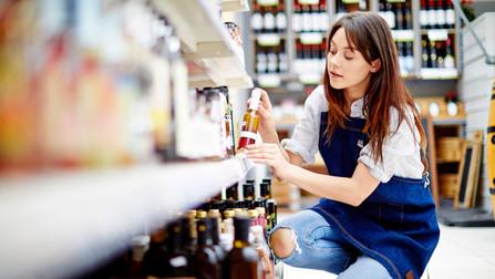 Eine Angestellte im Supermarkt räumt ein Regal ein.