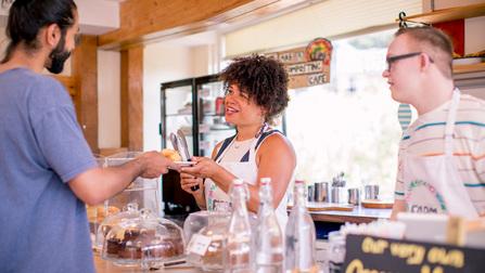 Zwei Verkäufer bedienen einen Kunden an einer Süßwarentheke.