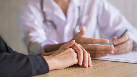 Hände eines Arztes und seines Patienten.