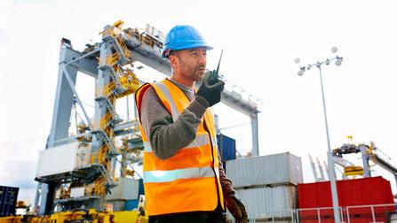 Ein Arbeiter an einem Containerhafen spricht in ein Funkgerät.