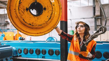 Eine Arbeiterin arbeitet in einer Industriehalle.