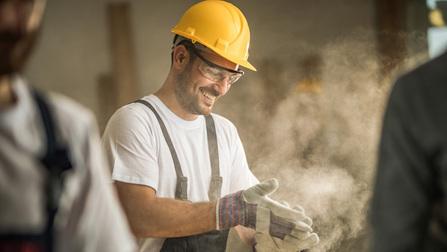 Ein Bauarbeiter klopft Staub aus seinen Arbeitshandschuhen.