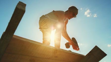Ein Dachdecker schraubt Holzbretter.