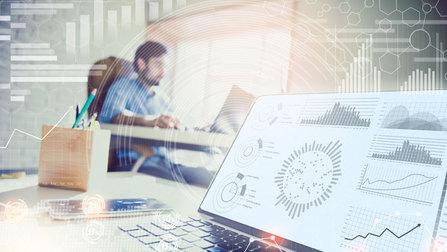 Mann in einem Büro, im Vordergrund ein Monitor mit Diagrammen.