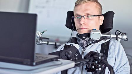 Ein Mann mit Behinderung bedient einen PC.