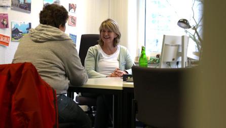 Zwei Frauen unterhalten sich an einem Schreibtisch.