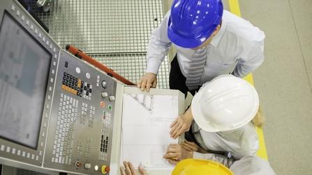Ingenieure, die im Werk eine CNC-Maschine programmieren.
