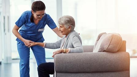 Eine Pflegerin hilft einer älteren Dame.
