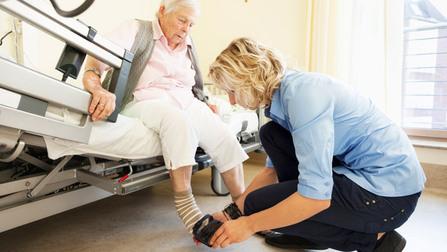 Eine Pflegerin im Altenheim zieht einer älteren Frau die Schuhe an.