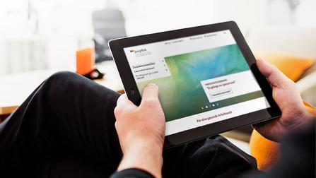 Ein Mann hält ein Tablet in den Händen, worauf die Website psyga.info zu sehen ist.