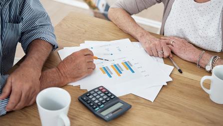 Zwei Rentner schauen sich Dokumente an.