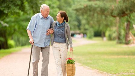 Eine Frau stützt einen alten Mann mit Krückstock und trägt eine Einkaufstasche.
