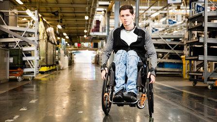 Ein Rollstuhlfahrer in einer Lagerhalle.
