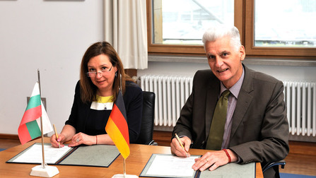 Staatssekretär Dr. Rolf Schmachtenberg und die stellvertretende bulgarische Ministerin für Arbeit und Soziales Zornitsa Rousinova unterzeichnen Dokumente.