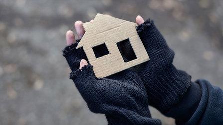 Hände eines Obdachlosen halten ein Karton-Haus.