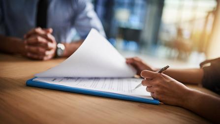 Eine Frau blättert in Unterlagen mit einem Stift in der Hand.