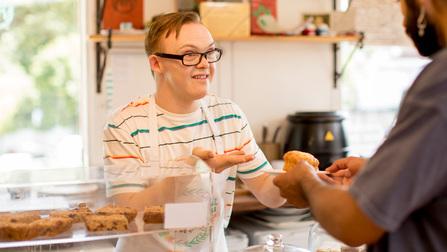 Mensch mit Behinderung als Verkäufer in einer Bäckerei.