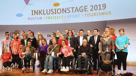 Minister Heil mit einigen Teilnehmerinnen und Teilnahmern auf der Bühne des Veranstaltungsortes.
