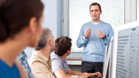 Teilnehmer eines Kurses sitzen vor Computern.
