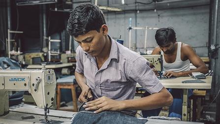 Indische Arbeiter nähen in einer Kleiderfabrik im Slum von Dharavi.