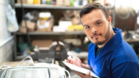 Ein junger Arbeiter steht in einer Werkstatt.