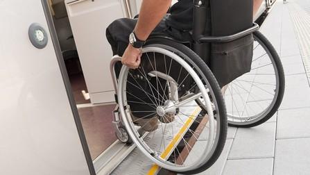 Ein Rollstuhlfahrer fährt über eine Rampe, um in einen Zug zu kommen.