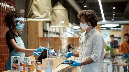 Eine Kassiererin bedient einen Kunden mit entsprechenden Schutzvorkehrungen zur Prävention des Corona-Virus.