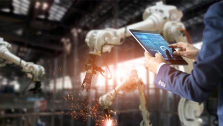 Ein Mann bedient in einer Fabrik Maschinen mit einem Tablet.