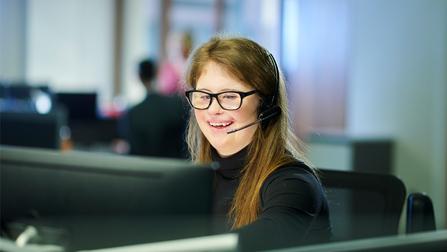 Eine Frau mit Down-Syndrom sitzt in einem B�ro und spricht in ein Headset.
