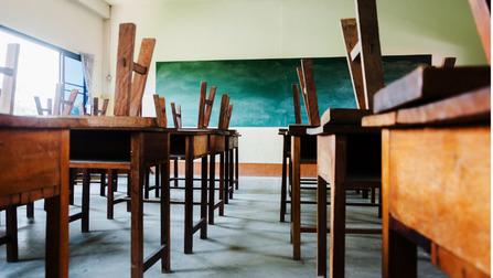 Ein leeres Klassenzimmer mit auf die Tische gestellten Stühlen.