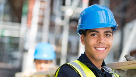 Junger Mann mit Schutzhelm auf einer Baustelle.