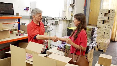 Eien Frau und ein Mann begrüßen sich in einer Werkstatt mit einem Händedruck.