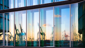 A port reflected in a building's glass facade Opens page: Free trade agreements