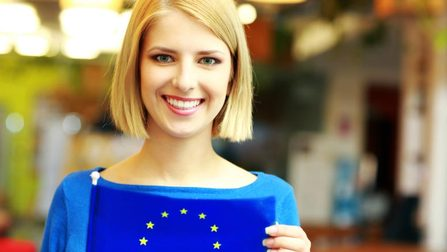 Woman holding a flag of the EU Opens page: Social Europe and International Affairs