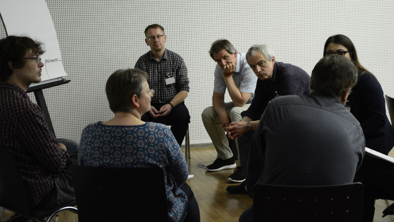 Personen diskutieren in einem Workshop.